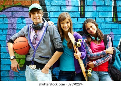 Row of happy teens by painted wall looking at camera