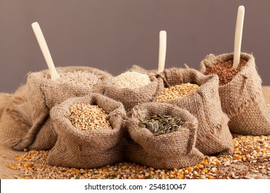 Row healthy grain food (corn, sesame, flax, buckwheat, wheat, pumpkin seeds, sunflower seeds ) in jute sack with wooden spoon