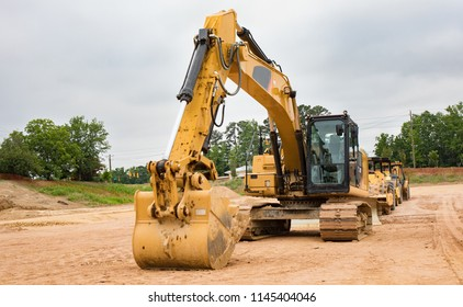 A row of heavy machinery equipment at a construction site.