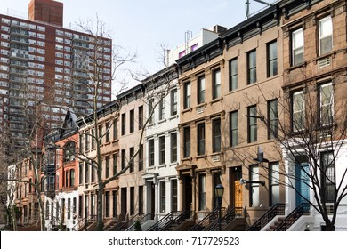 Row of historic brownstone buildings with colorful doors along a block in Manhattan, New York City NYC
