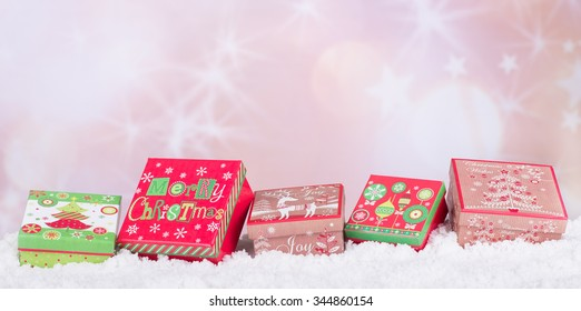 Row of holiday gift boxes on snow with colorful background for copy space