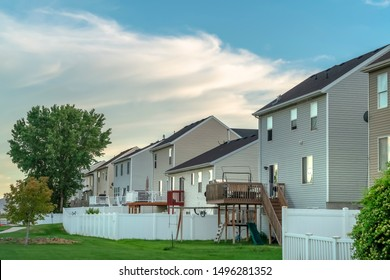 Row of homes with grassy yards balconies outdoor stairs and white fences