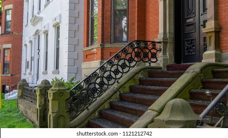 Row of houses with decorative stairs and entryways to 1800s Victorian era brick home district in Saint John, New Brunswick Canada