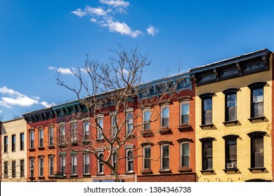 Row houses in Hoboken, New Jersey. Yellow, orange, red & beige facades mixed with a blue sky and a few puffy clouds offset the barren tree in early springtime. A diagonal composition adds perspective.