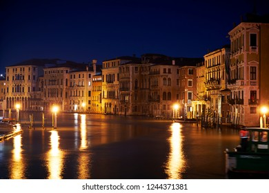 Row of houses with reflection on the Canal Grande in the night in Venice Nin Italy