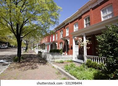 Row of houses. Richmond, Virginia. Brick sidewalk. Trees. Early spring. Blue sky. Horizontal.