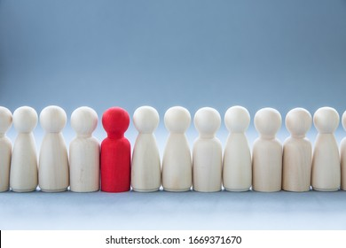 A row of human figures with a single individual standing out from the rest representing individuality and being different such as having a disease like coronavirus and infecting others