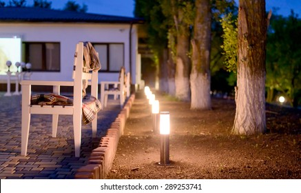 Row of Illuminated Outdoor Lights in Ground Alongside Stone Patio Furnished with Wooden Benches and Plaid Blankets Creating a Cozy and Inviting Atmosphere