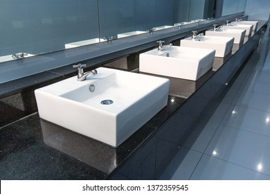 Row of indoor clean white basins with the faucets and mirrors in public toilet