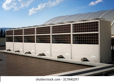 Row of industrial air conditioning condenser units on rooftop in front of blue sky