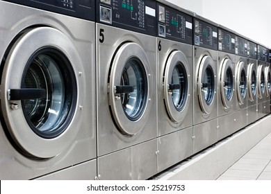 A row of industrial washing machines in a public laundromat