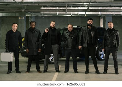 Row of intercultural armed gangsters or criminals in black jackets and jeans standing in front of camera on parking area