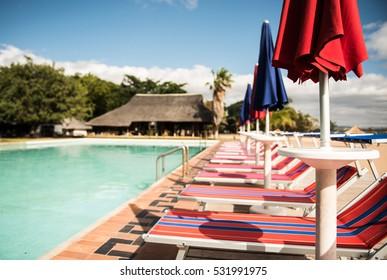 Row of Italian sun beds next to the resort pool