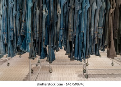 Row of jeans or denim trousers and slacks hang on hanger. Various Jeans in retail fashion store. Second hand denim sold in outlet shop.