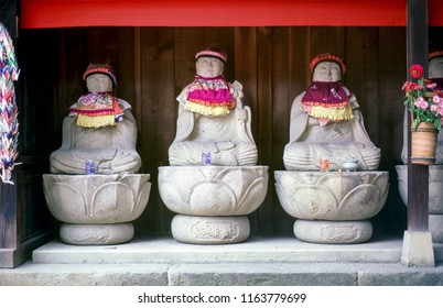 Row of Jizo monk statues with bib and hat - Japan. Jizo is a guardian of aborted children and kids who die prematurely.