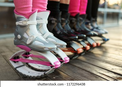 row of kangoo jumping boots at womens legs. group of girls at fitness workout