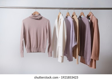 Row of knitted, turtleneck sweaters with white ,brown suit hang on hangers.
