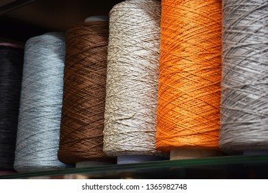 Row of large bobbins of polyethylene thread. Coils of warm and pastel tones with a closeup, selective focus.