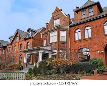 row of large brick Victorian houses with gables and dormer windows