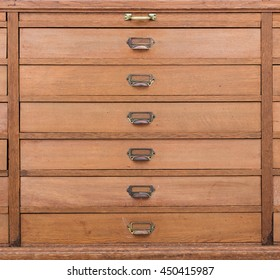 Row of large drawers with empty tags in an old furniture module