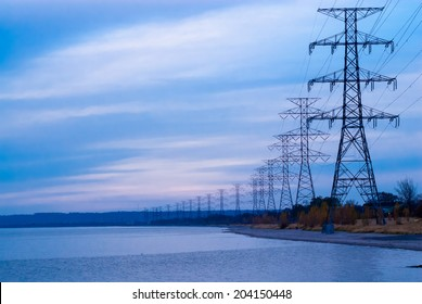 Row of large electrical towers receding into distance by shore.