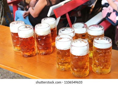 a row of large filled beer mugs standing on a table in a Bavarian beer garden, guests in the background
