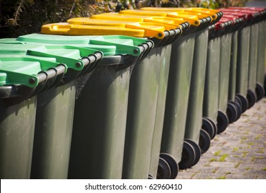 Row of large green wheelie bins for rubbish, recycling and garden waste