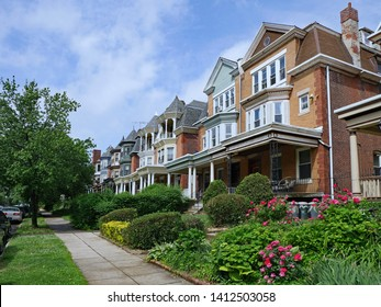 Row of large old brick houses with front porches and gardens
