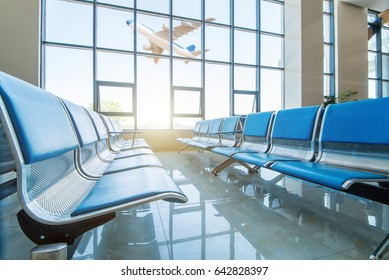 Row of leather chairs in international airport terminal at window background.
