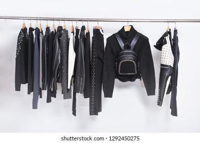 Row of leather punk jacket and black sweater ,pants, coat ,handbag on hanger