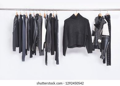 Row of leather punk jacket and black sweater ,pants, coat on hanger