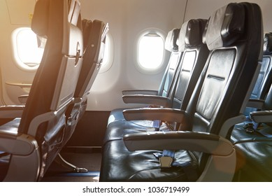 Row of leather seats in airplane interior. Side view of air plane chairs