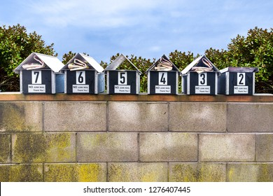 A row of letter boxes displaying no junk mail or circulars on a short wall in front of a house fence wall still have paper circulars put into them