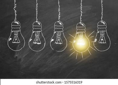 Row of light bulbs chalk drawing on  blackboard. Concept of idea.