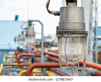 Row of lighting masts with lanterns in explosion-proof and fire-proof design close-up over background of pipelines buildings and equipment of chemical plant with copy space.