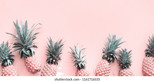 Row Line Pine Apple Whole Tropical Fruits with Leaves Useful Natural Organic Food Style Top View Flat Lay Group Objects. Background Toned pink turquoise trend colors