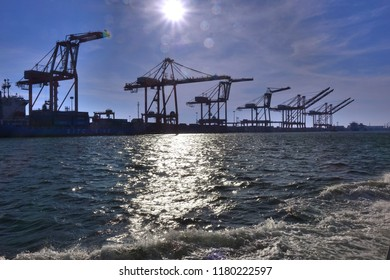 A row of loading cranes for containers are seen in port
