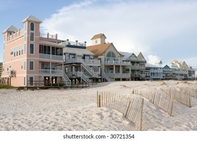 A row of luxury beach homes line the dunes along the Gulf Shores, Alabama coastline.