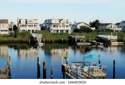 A row of luxury waterfront beach houses on the back bay in Avalon, New Jersey during a quiet summer sunset.