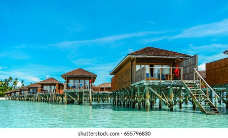 row of luxury wooden water bungalows in the water ocean of the Maldives, Luxury bungalows in the green blue ocean