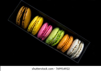 Row of macaroon cookies in rainbow colors. Pack in black cartoon box on black background. Top view on diagonal cookies line from above.