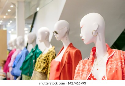 Row of mannequins displaying apparel at a department store.
