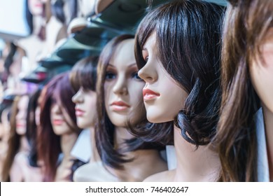 a row of mannequins women on a shelf in a wig shop