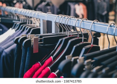 Row of many different clothes hanging on a hanger in a textile shop using classic wire and plastic hangers. Row of clothes in a shop.