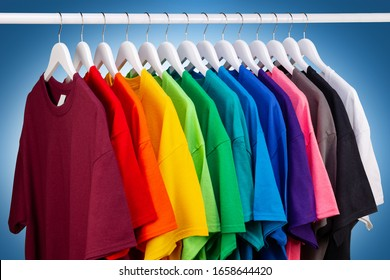 row of many fresh new fabric cotton t-shirts in colorful rainbow colors hangng on clothes rail in wrdrobe. Various colored shirts on blue white background. diy printing fashion concept.