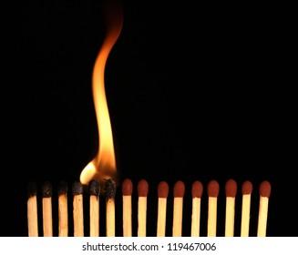 Row of matches starts burning, on black background