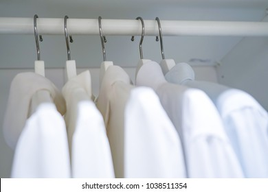 row of men and women shirts on the hanger, hanging in the wardrobe