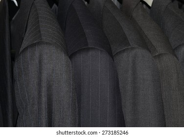 Row of mens suits on hangers in closet