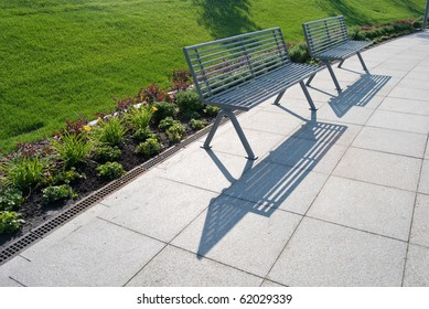 row of metal park benches with green grass behind