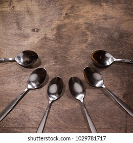 A row of metal spoons on a wooden old background